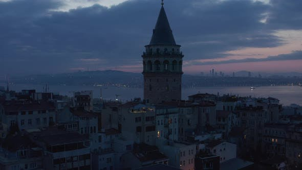 Establishing Shot of Galata Tower at Dark Blue Hour with Bosphorus in Background and Red Purple Sky