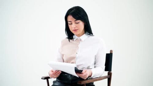 Attractive business woman reading in empty studio
