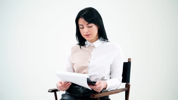 Thumbnail for Attractive business woman reading in empty studio