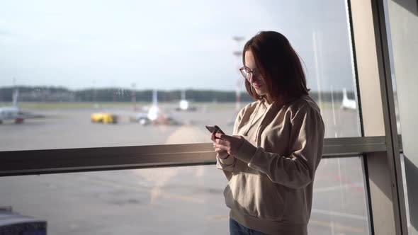 Thumbnail for Young Woman with a Phone in Her Hands on the Background of a Window at the Airport. Airplanes in the