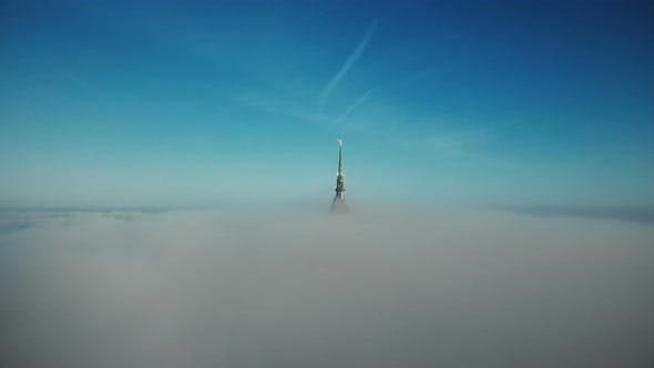 Thumbnail for Drone Flying To and Above Mont Saint Michel Golden Castle Spire Covered By Thick Fog Mist Clouds in