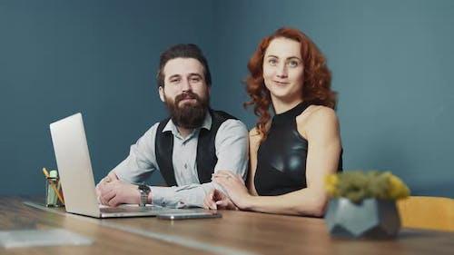 Porträt von zwei Arbeitern Mann mit Bart und Frau mit rotem Haar, die im Büro zusammenarbeiten