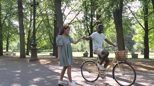 Black Man Rides Bike Holding Brunette Hand Riding Skateboard
