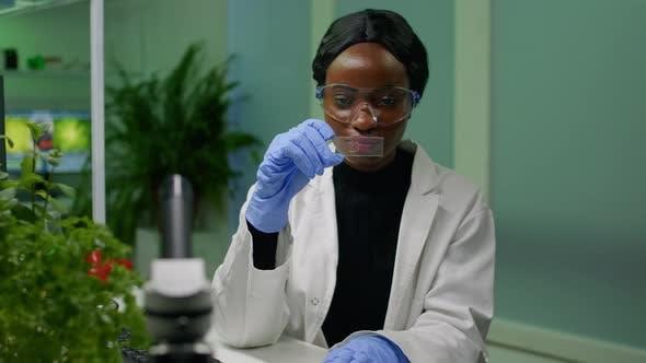 Botanist Researcher Scientist Analyzing Green Liquid Sample Under Microscope