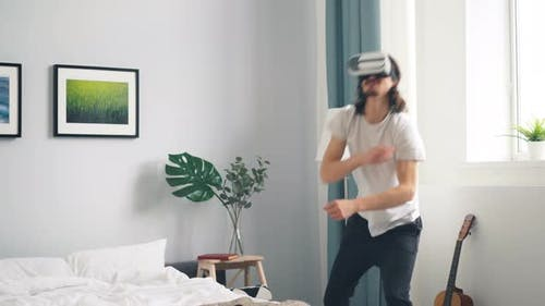 Man in Ar Glasses Playing War Video Game Shooting Gesturing in Bedroom at Home