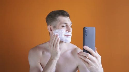 Young Man with White Shaving Foam on His Face Looking at His Smartphone, Isolated Background, Bare