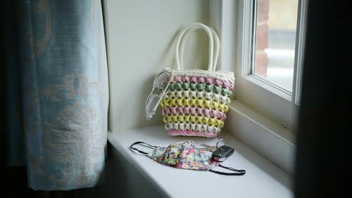 Woman grabbing cute bag and puts items in to leave house, face mask with flower pattern, sunny windo