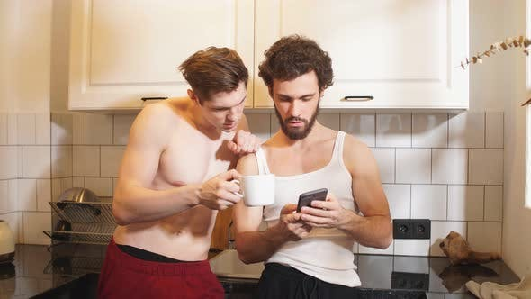 Couple Gay Handsome Men Talking for During Drinking Coffee at Kitchen in Morning.