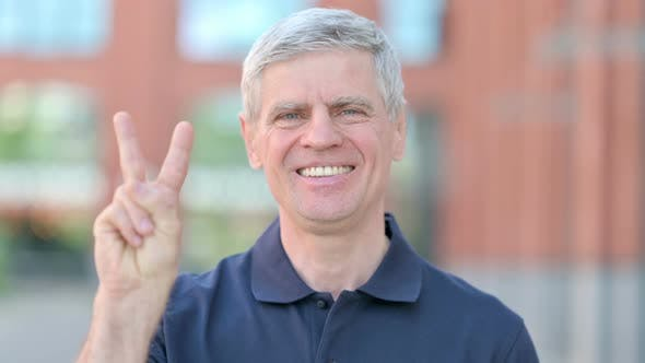 Outdoor Portrait of Cheerful Middle Aged Man Showing Victory Sign