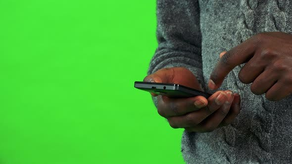 Thumbnail for A Black Man Works on a Smartphone - Closeup - Green Screen Studio