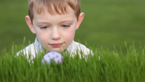 Thumbnail for Young boy finds Easter egg in grass