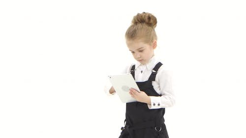 School Girl First Grader Communicates By Tablet on White Background