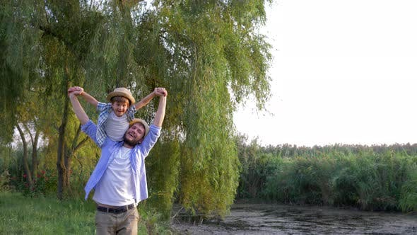 Thumbnail for Father and Son in Straw Hats Are Playing and Fooling Around on Open Air in Countryside