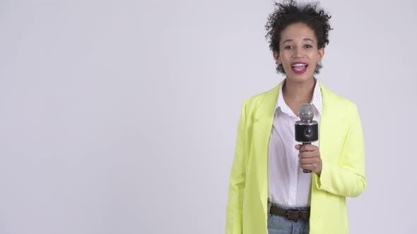Thumbnail for Happy Young Beautiful African Businesswoman As Newscaster Using Microphone