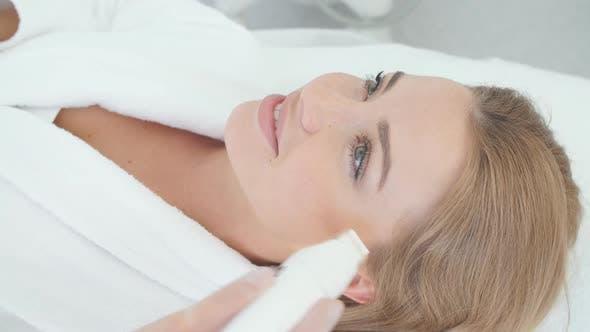 Thumbnail for Frau mit einer stimulierenden Gesichtsbehandlung von einem Therapeuten