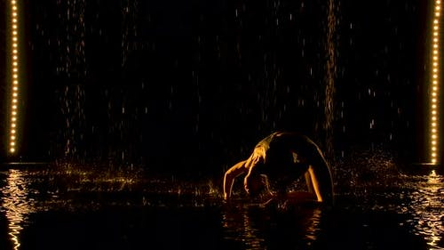 Silhouette of Attractive Woman Performing Bridge Pose. The Yellow Light Falls Softly on the Wet Body