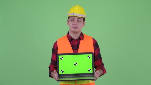 Thumbnail for Happy Young Multi Ethnic Man Construction Worker Thinking While Showing Laptop