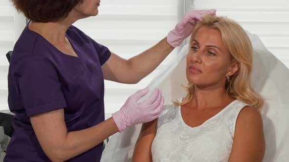 Cosmetologist Examining Face of Female Client