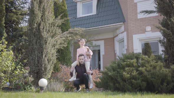 Thumbnail for Young Handsome Father Standing in Front of Big House with the Daughter Sitting on His Shoulders. The