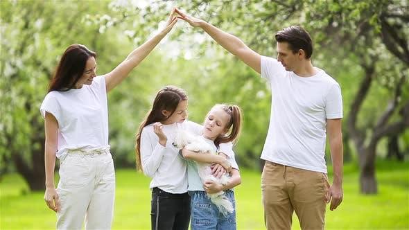 Entzückende Familie in blühenden Kirschgarten am schönen Frühlingstag