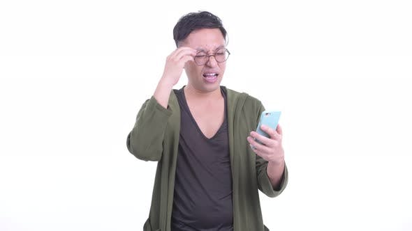 Thumbnail for Stressed Japanese Man with Eyeglasses Using Phone and Getting Bad News