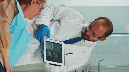 Vertikaler Video-Kieferorthopäde mit Tablet, um dem Patienten Zahnarztstrahlen zu erklären