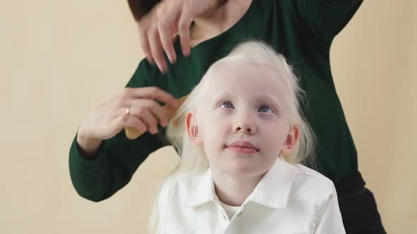 Young Cute Little Girl Model To Prepare for a Photo Shoot, She Is Doing a Hairstyle