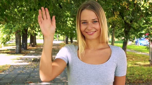 Thumbnail for Young Pretty Blond Woman Waves with Hand - Park with Trees in Background