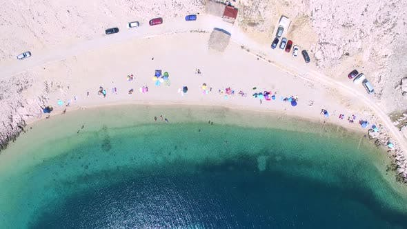 Thumbnail for Flying above umbrellas and people on isolated beach of Pag island, Croatia