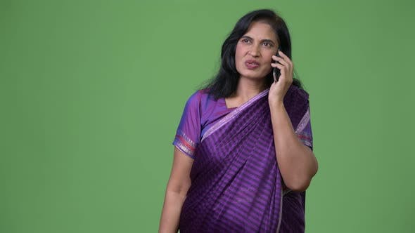 Cover Image for Mature Beautiful Indian Woman Talking on the Phone While Thinking