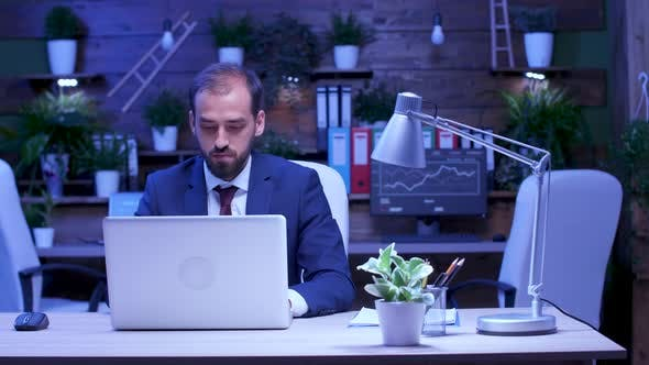 In Modern Loft Type Office Businessman Works Late at Night
