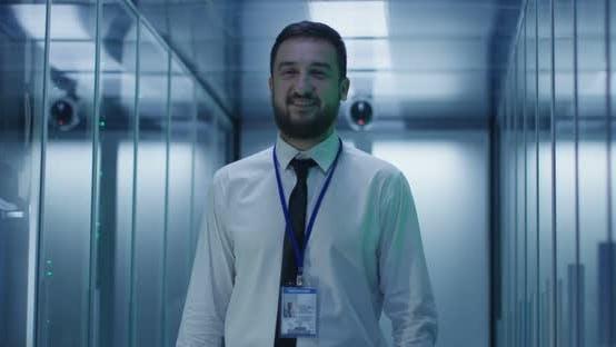Thumbnail for Smiling Engineer in Corridor of Data Center