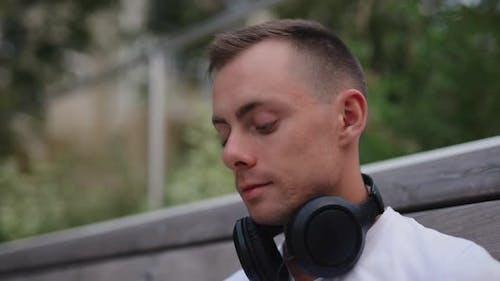 Man Listening Audio Book in Headphones Sitting on Bench