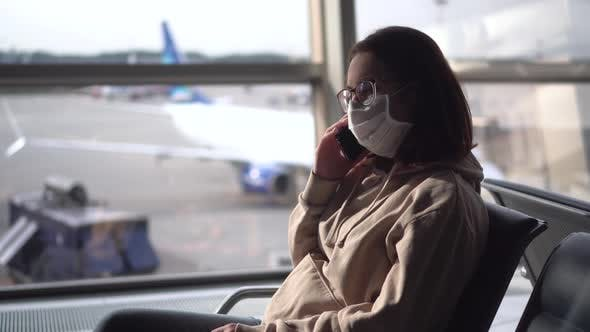 Thumbnail for A Young Woman Sits and Speaks on the Phone Against the Background of a Window at the Airport