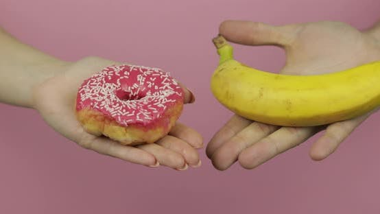 Hands Holds Donut and Banana. Choice Donut Against Banana. Healthy or Junk Food