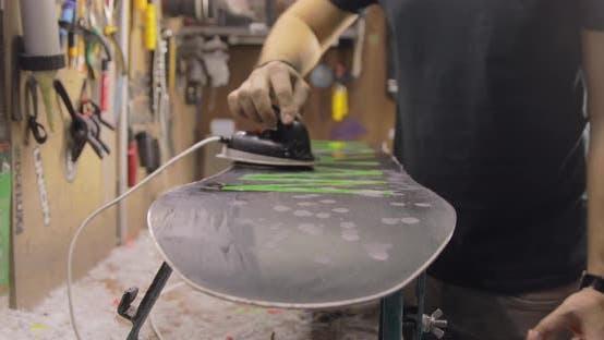 Thumbnail for Reparaturmann macht Wachsen und Bügeln. Snowboard Wartung und Reparatur Konzept.