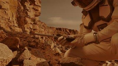 Unrecognizable Astronaut Analyzing Soil of Mars