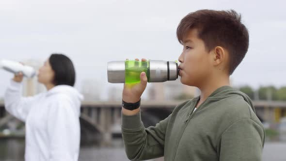 Thumbnail for Asian Boy Drinking Water after Running with Mother