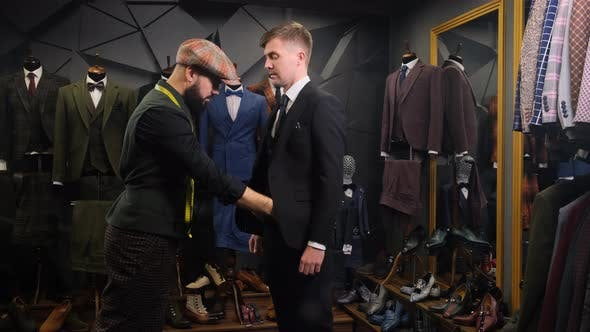 A Bearded Tailor Dresses a Handsome Young Man in a Quality Handmade Suit in an Atelier, Creative