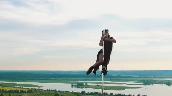 Thumbnail for Pole Dance on Nature - Sexy Woman with Long Blue Braids in Black Clothes Posing on the Top of the
