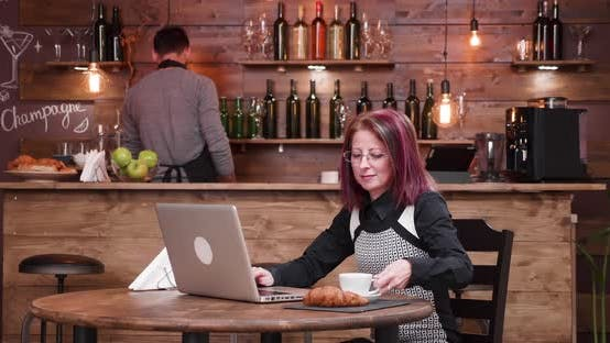 Medium Shot of Adult Businesswoman Typing an Email While Enjoying Her Coffee