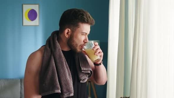Starker Mann trinkt Multivitamingetränk