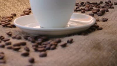 A cup of coffee with coffee beans in a rustic style in a cafe on a bar counter.
