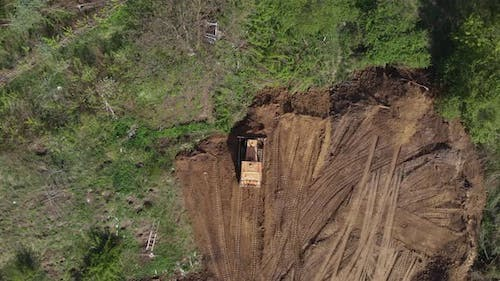 Top aerial view of bulldozer flattening surface on further construction site
