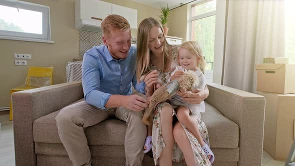 Thumbnail for Happy Cute Small Girl Run Exploring New House While Parents Embracing on Sofa, Family with Active