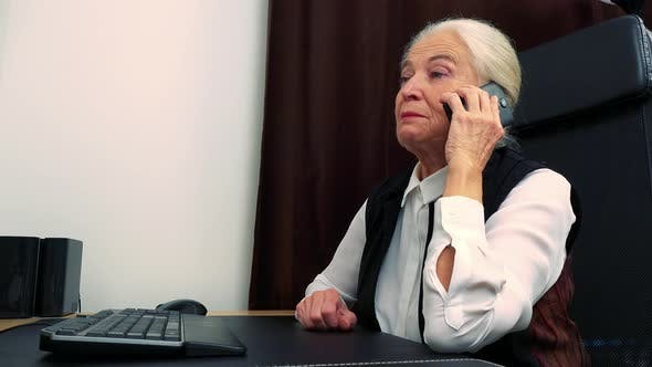 Thumbnail for Old Happy Caucasian Woman Works on Computer in Home and She Phone Call