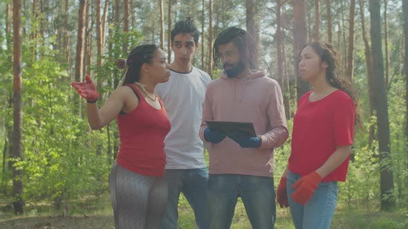 Eco Activists Discussing Forest Garbage Cleaning