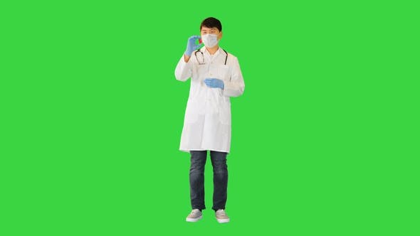 Young Asian Doctor Comparing Two Ampules with Red and Blue Solution on a Green Screen Chroma Key