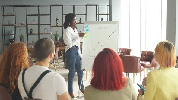 Young Successful Female Entrepreneur of African Descent Giving a Speech To Corporate Employees