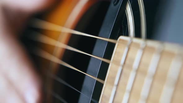 Musician Hand Beats Acoustic Guitar Body and Nylon Strings